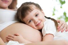 Ευτυχές κορίτσι παιδιών που αγκαλιάζει την κοιλιά της έγκυου μητέρας Στοκ εικόνες με δικαίωμα ελεύθερης χρήσης