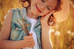 Ευτυχές κορίτσι παιδιών που περπατά στο θερινό λιβάδι με τα dangelions Αγροτική σκηνή ύφους χωρών, υπαίθριες δραστηριότητες Στοκ Εικόνες