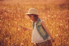 Ευτυχές κορίτσι παιδιών που περπατά στο θερινό λιβάδι με τις πικραλίδες Αγροτική σκηνή ύφους χωρών, υπαίθριες δραστηριότητες Στοκ Εικόνες