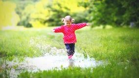 Ευτυχές κορίτσι παιδιών που τρέχει και που πηδά στις λακκούβες μετά από τη βροχή Στοκ Φωτογραφία