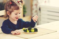Ευτυχές κορίτσι παιδιών που τρώει τα λαχανικά και τα γέλια στοκ εικόνα