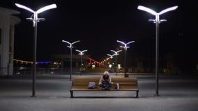 Ευτυχές κορίτσι που έχει τη διασκέδαση με κινητό app στη συσκευή, που κάθεται στον πάγκο στην πόλη νύχτας απόθεμα βίντεο