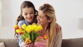 Ευτυχές κορίτσι που δίνει τα λουλούδια στη μητέρα στο σπίτι απόθεμα βίντεο