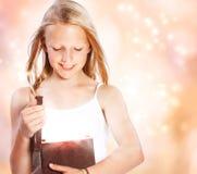 Ευτυχές κορίτσι που ανοίγει ένα παρόν στοκ εικόνες με δικαίωμα ελεύθερης χρήσης