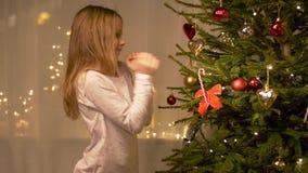 Ευτυχές κορίτσι που διακοσμεί το χριστουγεννιάτικο δέντρο στο σπίτι φιλμ μικρού μήκους