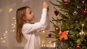 Ευτυχές κορίτσι που διακοσμεί το χριστουγεννιάτικο δέντρο στο σπίτι απόθεμα βίντεο