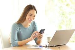 Ευτυχές κορίτσι που ελέγχει το σε απευθείας σύνδεση περιεχόμενο σε ένα έξυπνο τηλέφωνο στοκ εικόνες