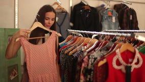 Ευτυχές κορίτσι που επιλέγει το νέο ένδυμα στο κατάστημα μόδας φιλμ μικρού μήκους