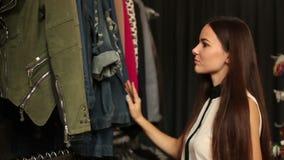 Ευτυχές κορίτσι που επιλέγει το νέο ένδυμα στο κατάστημα μόδας απόθεμα βίντεο