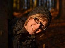 Ευτυχές κορίτσι που κοιτάζει πίσω από το δέντρο Στοκ εικόνα με δικαίωμα ελεύθερης χρήσης