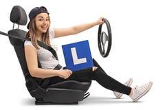 Ευτυχές κορίτσι που κρατά ένα λ-σημάδι και που προσποιείται να οδηγήσει Στοκ Εικόνες