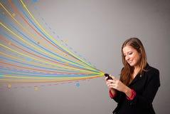 Ευτυχές κορίτσι που κρατά ένα τηλέφωνο με τις ζωηρόχρωμες αφηρημένες γραμμές Στοκ εικόνα με δικαίωμα ελεύθερης χρήσης