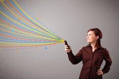 Ευτυχές κορίτσι που κρατά ένα τηλέφωνο με τις ζωηρόχρωμες αφηρημένες γραμμές Στοκ φωτογραφία με δικαίωμα ελεύθερης χρήσης