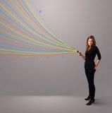 Ευτυχές κορίτσι που κρατά ένα τηλέφωνο με τις ζωηρόχρωμες αφηρημένες γραμμές Στοκ εικόνες με δικαίωμα ελεύθερης χρήσης