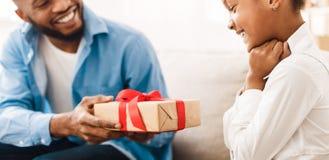 Ευτυχές κορίτσι που λαμβάνει το δώρο από τον πατέρα στο σπίτι στοκ φωτογραφίες