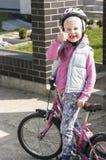 Ευτυχές κορίτσι που οδηγά ένα ποδήλατο Στοκ Φωτογραφία