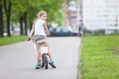 Ευτυχές κορίτσι που οδηγά ένα ποδήλατο, copyspace Στοκ Φωτογραφία