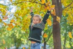 Ευτυχές κορίτσι που πηδά με τα κίτρινα φύλλα στοκ εικόνες