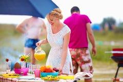 Ευτυχές κορίτσι που προετοιμάζει τα τρόφιμα στον πίνακα πικ-νίκ Στοκ φωτογραφία με δικαίωμα ελεύθερης χρήσης