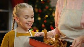 Ευτυχές κορίτσι που προσέχει πώς κοτόπουλο μαγειρέματος μητέρων, προετοιμασία για το γεύμα Χριστουγέννων απόθεμα βίντεο