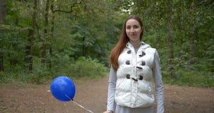 Ευτυχές κορίτσι που στέκεται με ένα μπλε μπαλόνι και που χαμογελά σε ένα ξύλο στην slo-Mo απόθεμα βίντεο