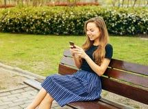 Ευτυχές κορίτσι που στέλνει το μήνυμα στο πάρκο Στοκ Εικόνες