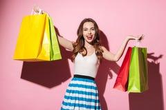 Ευτυχές κορίτσι που φέρνει τις ζωηρόχρωμες τσάντες αγορών που απομονώνονται πέρα από το ρόδινο υπόβαθρο Στοκ Εικόνα