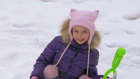 Ευτυχές κορίτσι που χαμογελά και που παρουσιάζει αντίχειρες στο χειμερινό υπόβαθρο φιλμ μικρού μήκους