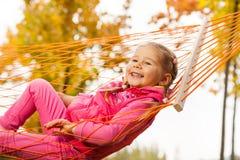 Ευτυχές κορίτσι που χαλαρώνει και που βάζει σε καθαρό της αιώρας Στοκ φωτογραφία με δικαίωμα ελεύθερης χρήσης