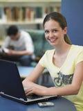Ευτυχές κορίτσι που χρησιμοποιεί το lap-top στη βιβλιοθήκη στοκ φωτογραφία