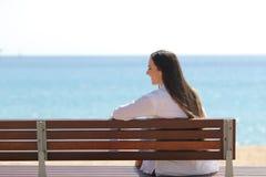 Ευτυχές κορίτσι σε έναν πάγκο που συλλογίζεται τον ωκεανό στην παραλία στοκ εικόνα