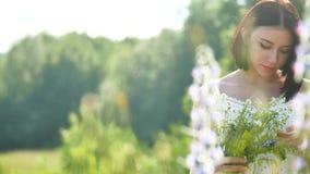Ευτυχές κορίτσι σε έναν τομέα με τα λουλούδια στη φύση κορίτσι σε μια χαμογελώντας γυναίκα τομέων που κρατά μια υπαίθρια ανθοδέσμ Στοκ Εικόνα