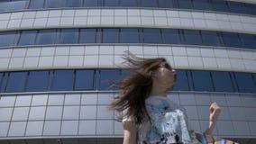 Ευτυχές κορίτσι σε μια οδό πόλεων με τις συσκευασίες και τις αγορές απόθεμα βίντεο