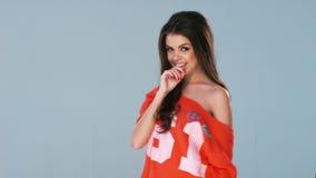 Ευτυχές κορίτσι στην πορτοκαλιά τοποθέτηση πουκάμισων απόθεμα βίντεο