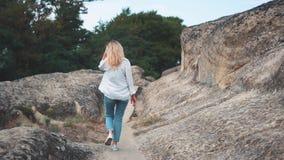 Ευτυχές κορίτσι στις διακοπές, που περπατούν στα βουνά ενάντια στο σκηνικό των βράχων Κοιτάζει γύρω με ένα ευρύ χαμόγελο σε δικοί απόθεμα βίντεο