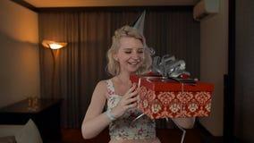 Ευτυχές κορίτσι στον ενθουσιασμό που παίρνει το κιβώτιο Χριστουγέννων απόθεμα βίντεο