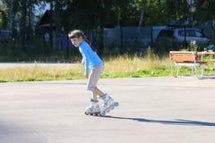 Ευτυχές κορίτσι στον μπλε κύλινδρο που κάνει πατινάζ στην παιδική χαρά Στοκ Εικόνες