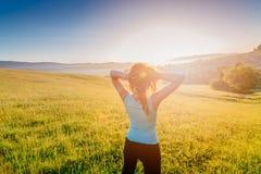 Ευτυχές κορίτσι στο θερινό λιβάδι που απολαμβάνει το πρωί ομορφιάς στα βουνά στοκ φωτογραφία