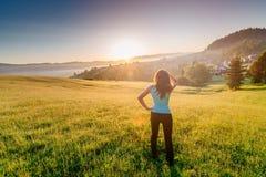 Ευτυχές κορίτσι στο θερινό λιβάδι που απολαμβάνει το πρωί ομορφιάς στα βουνά στοκ εικόνες