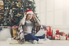 Ευτυχές κορίτσι στο καπέλο santa που κουβεντιάζει on-line στο lap-top Στοκ εικόνες με δικαίωμα ελεύθερης χρήσης