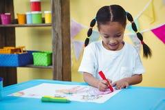 Ευτυχές κορίτσι στο χρωματισμό γραφείων της Στοκ εικόνες με δικαίωμα ελεύθερης χρήσης
