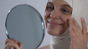 Ευτυχές κορίτσι στο headwrap που εξετάζει την αντανάκλαση καθρεφτών, επιτυχής πλαστική χειρουργική φιλμ μικρού μήκους