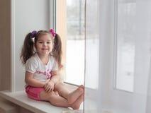 Ευτυχές κορίτσι στο windowsill στοκ εικόνες με δικαίωμα ελεύθερης χρήσης