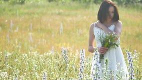 Ευτυχές κορίτσι υπαίθριο σε έναν τομέα με τα λουλούδια στη φύση κορίτσι σε μια χαμογελώντας γυναίκα τομέων που κρατά μια ανθοδέσμ Στοκ φωτογραφία με δικαίωμα ελεύθερης χρήσης