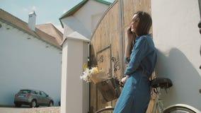Ευτυχές κορίτσι brunette που γελά και που μιλά στο τηλέφωνο που στέκεται κοντά στην παλαιά πύλη με το ποδήλατο και τα λουλούδια σ φιλμ μικρού μήκους