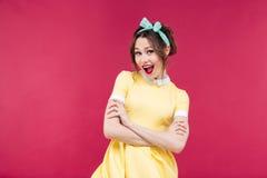 Ευτυχές κορίτσι pinup στο κίτρινο φόρεμα που στέκεται με τα όπλα που διασχίζονται Στοκ Εικόνα