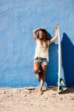 Ευτυχές κορίτσι surfer με την ιστιοσανίδα μπροστά από τον μπλε τοίχο Στοκ Φωτογραφίες