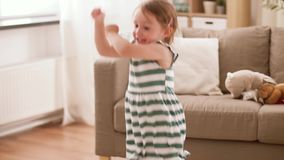 Ευτυχές κοριτσάκι που πηδά και που έχει τη διασκέδαση στο σπίτι απόθεμα βίντεο