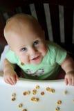 Ευτυχές κοριτσάκι στην υψηλή έδρα που τρώει τα δημητριακά στοκ φωτογραφίες