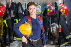 Ευτυχές κράνος εκμετάλλευσης Firewoman στο πυροσβεστικό σταθμό στοκ φωτογραφία με δικαίωμα ελεύθερης χρήσης